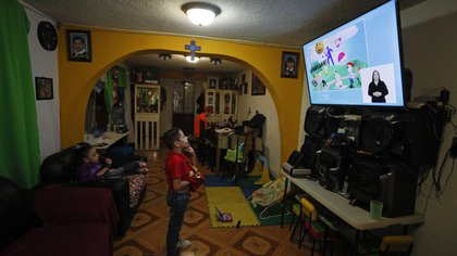Santi, 6, follows a televised kindergarten lesson in his home as students return to classes but not schools in Mexico City, Monday, Aug. 24, 2020. A system cobbling together online classes, instruction broadcast on cable television channels and radio programming in indigenous languages for the most remote, will attempt to keep students from missing out. (AP Photo/Rebecca Blackwell)