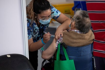 Una enfermera le administra una vacuna contra la covid-19 a un adulto mayor en un centro de vacunación masivo localizado en la comuna de La Florida, en Santiago (Chile). EFE/Alberto Valdés/Archivo