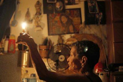 Elizabeth Guzman Espitia con una vela en su casa (AP /Ariana Cubillos)
