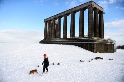 Una persona pasea su mascota en la nieve de Edimburgo (Andy Buchanan / AFP)