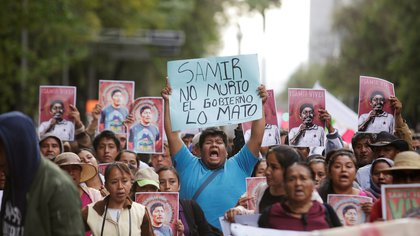 A man holds up a placard reading 'Samir didn't die, the government killed him' during a protest to demand justice for Mexican activist Samir Flores Soberanes in Mexico City