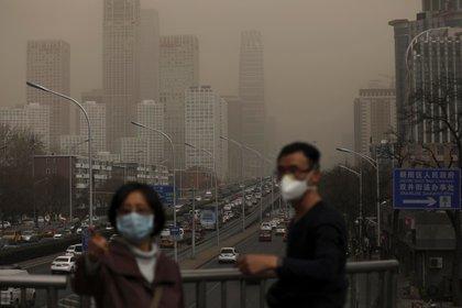Un hombre y una mujer se protegen con máscaras de la nube de contaminación que cubre la ciudad de Pekín, China (EFE/Archivo/Wu Hong)