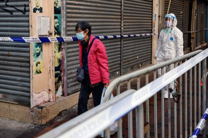 A resident carries a bag of grocery inside a locked down portion of the Jordan residential area to contain a new outbreak of the coronavirus disease (COVID-19), in Hong Kong, China January 23, 2021. REUTERS/Tyrone Siu