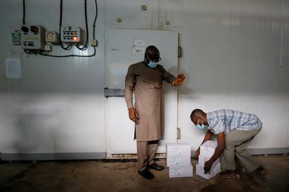 A worker prepares to store boxes of vaccines in a cold room as the country receives its first batch of coronavirus disease (COVID-19) vaccines under COVAX scheme, in Accra, Ghana February 24, 2021. REUTERS/Francis Kokoroko