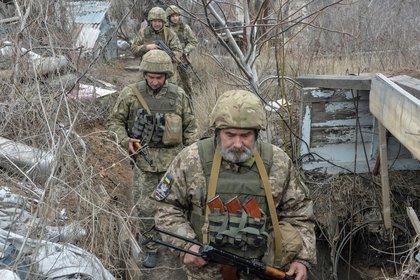 Miembros de las fuerzas armadas ucranianas caminan en posiciones de combate en la línea de separación de los rebeldes prorrusos cerca de Donetsk (REUTERS/Oleksandr Klymenko)