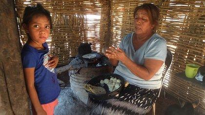 Una mujer de la tribu Yaqui elabora Tortillas, acompañada de una niña, este miércoles en el municipio de Cajeme estado de Sonora (México). EFE/Daniel Sánchez
