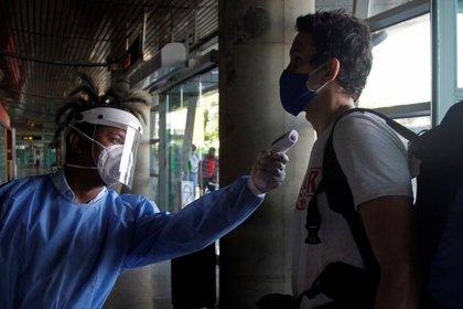 Un empleado le toma la temperatura a un pasajero a su ingreso, el 1 de septiembre, al aeropuerto internacional Rafael Núñez de Cartagena (Colombia). EFE/Ricardo Maldonado Rozo