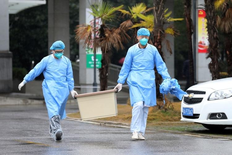 Un equipo médico lleva una caja mientras camina hacia el hospital Jinyintan, donde hay pacientes con neumonía causada por la nueva cepa de coronavirus bajo tratamiento, en Wuhan, provincia de Hubei, China (REUTERS/Stringer/China Out)