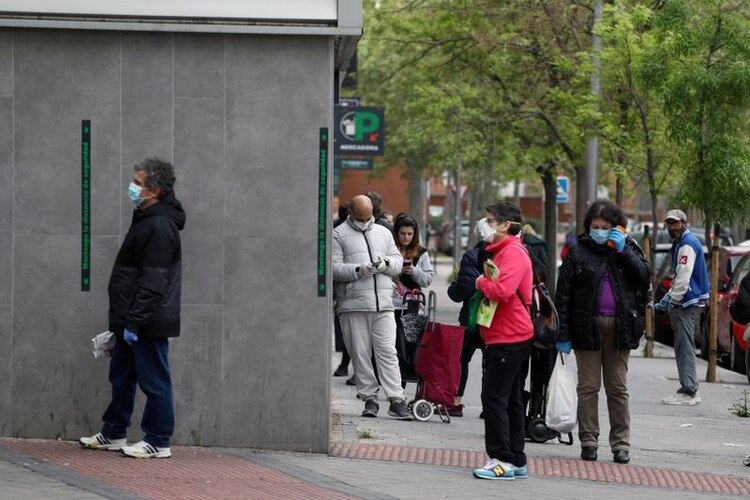 La gente mantiene la distancia social mientras espera entrar en un supermercado en medio del brote de la enfermedad coronavirus (COVID-19) en Madrid, España (REUTERS/Sergio Pérez)