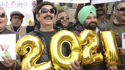 La gente sostiene pancartas y globos que forman el número 2021 durante las celebraciones del Año Nuevo en Amritsar, India (NARINDER NANU/ AFP)
