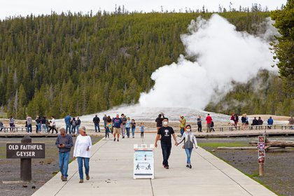 Los visitantes que llevan máscaras observan la erupción del géiser Old Faithful en la reapertura del Parque Nacional Yellowstone, Wyoming, EE. UU. 18 de mayo de 2020. Fotografía tomada el 18 de mayo de 2020. (NPS / Jacob W. Frank / REUTERS)