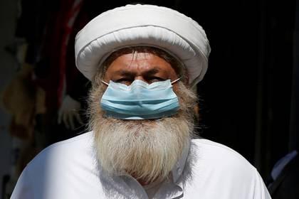 Un hombre lleva una máscara protectora mientras camina por el mercado principal en el centro de Amán, en Jordania