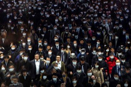 Pasajeros con mascarillas en la estación Shinagawa de Tokio para prevenir el contagio con el covid-19 (2 de marzo)