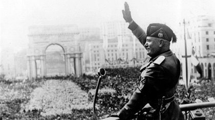Benito Mussolini, haciendo el saludo fascista ante la multitud desde un balcón
