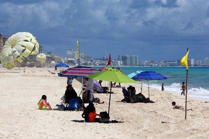 Las playas y los espacios públicos del Caribe mexicano fueron reabiertos este lunes a los visitantes tras reducirse de alta a media la situación de riesgo de contagio del coronavirus en el estado de Quintana Roo. (Foto: EFE)