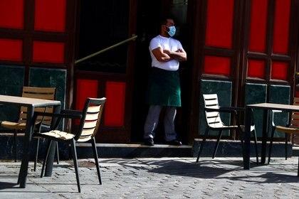 Un mesonero espera la llegada de clientes en una terraza usando un tapabocas
