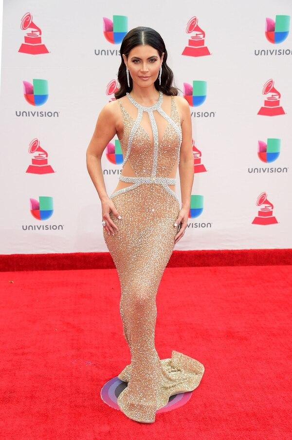 Chiquinquira Delgado la reconocida presentadora venezolana dejó lucir su figura con un diseño al cuerpo con un mix de bordados, transparencias y cortes irregulares. Eligió para los accesorios, dos joyas, un anillo y aros gota de brillantes.