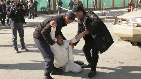 Tras la detonación de un coche bomba, un herido es asistido en la cercanía de la Plaza Sadarat (AP)
