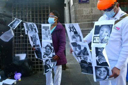 Trabajadores de la Salud muestran imágenes de compañeros fallecidos durante una protesta, este viernes, a las afueras de Palacio Nacional, en Ciudad de México (México). EFE/ Jorge Núñez