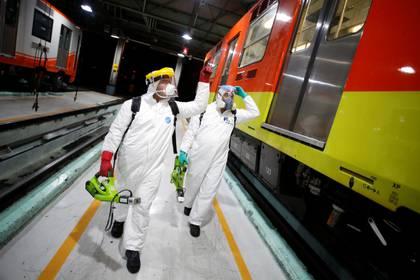 Los trabajadores caminan afuera de los vagones del metro antes de realizar una desinfección como parte de las medidas del gobierno de la Ciudad de México en respuesta al coronavirus (COVID-19), en la Ciudad de México, México, 17 de marzo de 2020.