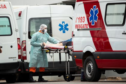Personal médico de una ambulancia traslada a un paciente para remitirlo a un hospital en Brasilia (EFE/Joédson Alves)