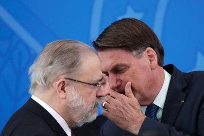 Jair Bolsonaro hablando con el procurador general Augusto Aras durante la ceremonia de jura de ministro de Salud, Nelson Teich en Brasilia. Ninguno de los dos usó máscaras faciales ni respetó la distancia social REUTERS/Ueslei Marcelino