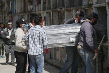 Trabajadores del cementerio y familiares portan el ataúd de una mujer, fallecida por la enfermedad del coronavirus (COVID-19), durante su funeral en el cementerio Municipal de Nezahualcóyotl, en las afueras de la Ciudad de México, México, 27 de enero de 2021. REUTERS / Henry Romero