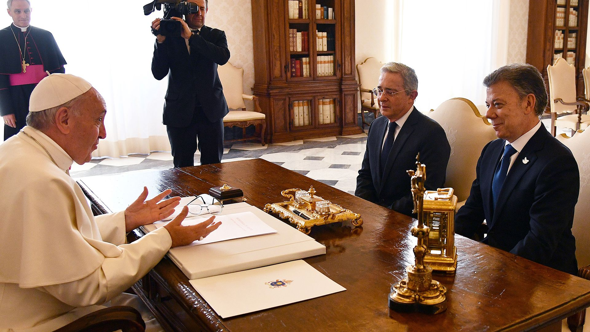Pope Francis (l) speaks with Colombian president Juan Manuel Santos (R) and former president Alvaro Uribe prior to a meeting, on January 16, 2016 at the Vatican. / AFP PHOTO / POOL / VINCENZO PINTO