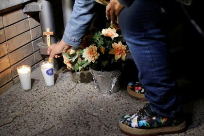 A woman places a candle and flowers at the scene of the shooting, outside the Colegio Cervantes Photo: (REUTERS / Daniel Becerril)