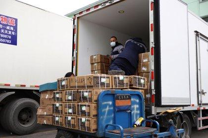 Trabajadores transportan productos congelados en un camión en un mercado mayorista de alimentos congelados en Beijing, China, el 26 de noviembre de 2020. Fotografía tomada el 26 de noviembre de 2020. REUTERS / Florence Lo