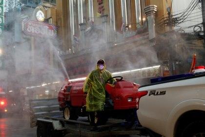 Un hombre con una máscara facial protectora y un traje fumiga el barrio chino de Bangkok, Tailandia (Reuters)