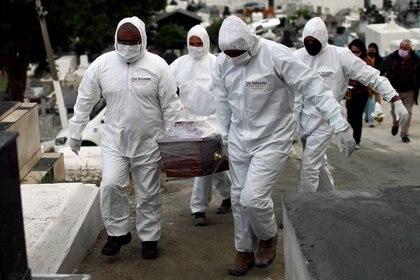 Funcionarios de un cementerio vistiendo ropa de protección durante el entierro de una víctima por COVID-19, en Nova Iguaçu, Río de Janeiro, Brasil, el 16 Julio de 2020 (REUTERS/Pilar Olivares)