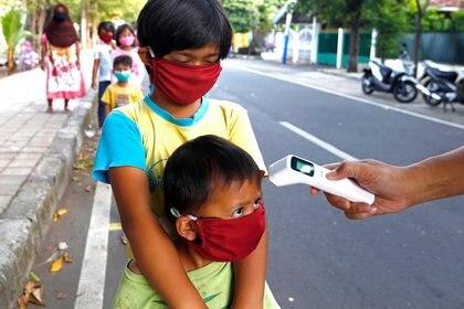 Niños con máscaras protectoras contra el coronavirus pasan un control de temperatura en Jakarta, Indonesia REUTERS/Ajeng Dinar Ulfiana