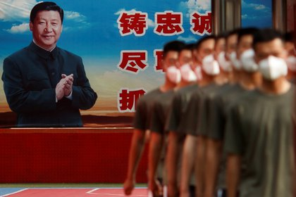 Oficiales de la Policía Paramilitar marchan en formación cerca de un cartel del Presidente chino Xi Jinping en la puerta de la Ciudad Prohibida el día de la inauguración del Congreso Nacional del Pueblo (NPC) tras el brote de la enfermedad coronavirus (COVID-19), en Beijing, China, el 22 de mayo de 2020. (REUTERS)