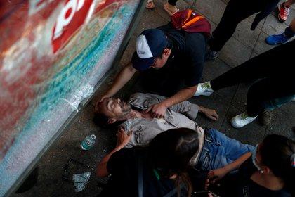 Un hombre herido yace en el suelo después de chocar con la policía durante una protesta en Santiago (REUTERS/Jorge Silva)