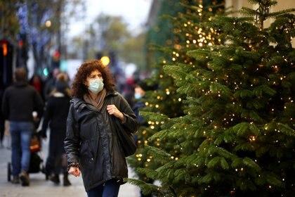 FOTO DE ARCHIVO: Una mujer pasa junto a los árboles de Navidad en Oxford Street, en medio del brote de la enfermedad por coronavirus (COVID-19), en Londres, Gran Bretaña. REUTERS/Henry Nicholls
