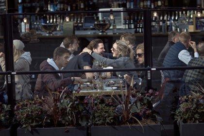 ARCHIVO - En esta imagen de archivo del 4 de abril de 2020, una pareja ríe y se abraza mientras come en un restaurante en Estocolmo.  (AP Foto/Andrés Kudacki, Archivo)