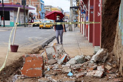 A woman walks by debris from a building damaged during a quake, in Oaxaca, Mexico June 23, 2020. REUTERS/Jorge Luis Plata