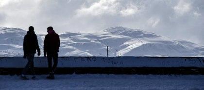 Dos personas caminando en la nieve (Andy Buchanan / AFP)