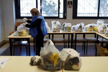 Un voluntario con mascarilla protectora y guantes prepara bolsas para la distribución de alimentos organizada por la comunidad de Sant'Egidio en la parroquia de San Gaudenzio durante el encierro para prevenir la propagación de la enfermedad por coronavirus (COVID-19), en Roma, Italia, el 23 de marzo. 2020. (REUTERS / Yara Nardi)