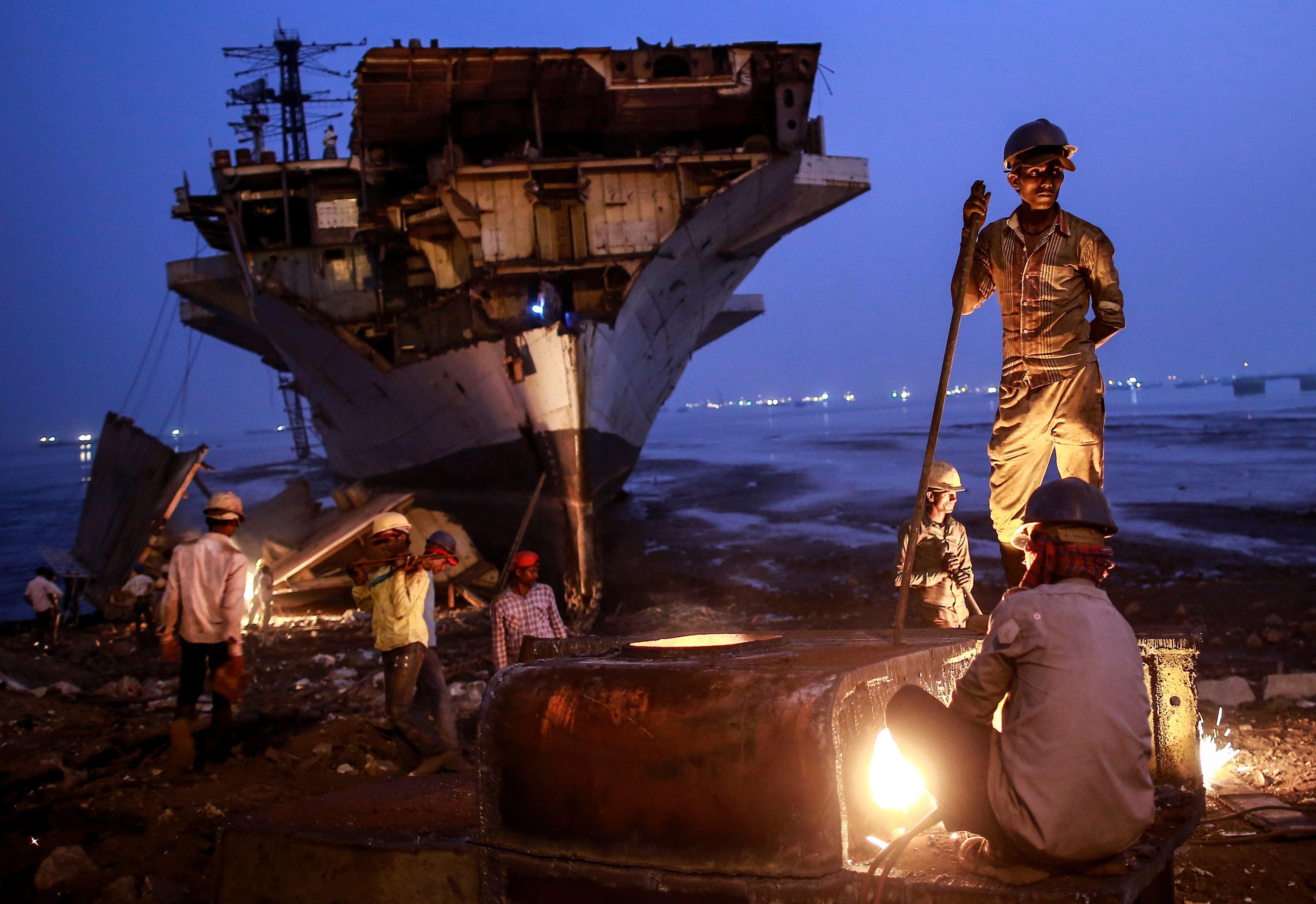 Un trabajador utiliza un cortador de metal mientras otros llevan a desmantelar partes del buque de la Armada India INS Vikrant retirado del servicio en un astillero de desguace en Mumbai 24 de noviembre de 2014.