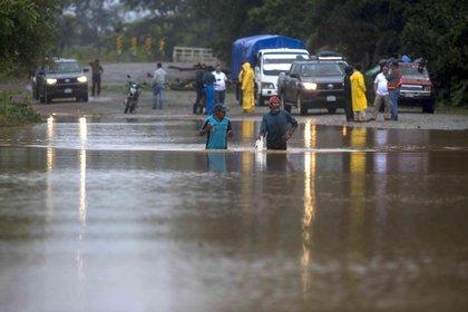 os hombres cruzan por un camino inundado en la comunidad Okonwas, durante el paso del huracán Eta sobre la costa caribe norte en Rosita (Nicaragua). EFE/Jorge Torres