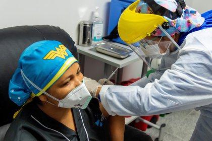 Fotografía cedida por la presidencia de Colombia de Liseidis Pérez, trabajadora de limpieza hospitalaria en el momento que recibe la vacuna contra la covid-19 hoy en Barranquilla (Colombia). EFE/Nicolás Galeano/Presidencia de Colombia