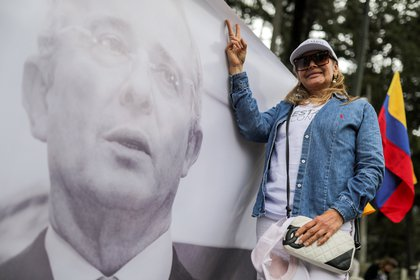FILE PHOTO: A supporter of Alvaro Uribe, Colombia's former president and lawmaker, gestures next to an image of him, as he attends a private hearing at the Supreme Court of Justice, at the National park, in Bogota, Colombia October 8, 2019. REUTERS/Luisa Gonzalez/File Photo