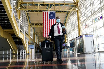 Un pasajero con una mascarilla camina en el aeropuerto Reagan, en Washington (Reuters)