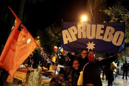 """Un grupo de personas sostiene un cartel que dice """"Apruebo"""" para celebrar el resultado del plebiscito que permitirá la redacción de una nueva Constitución política en Chile, en Valparaíso, Chile, el 25 de octubre de 2020. REUTERS/Rodrigo Garrido"""