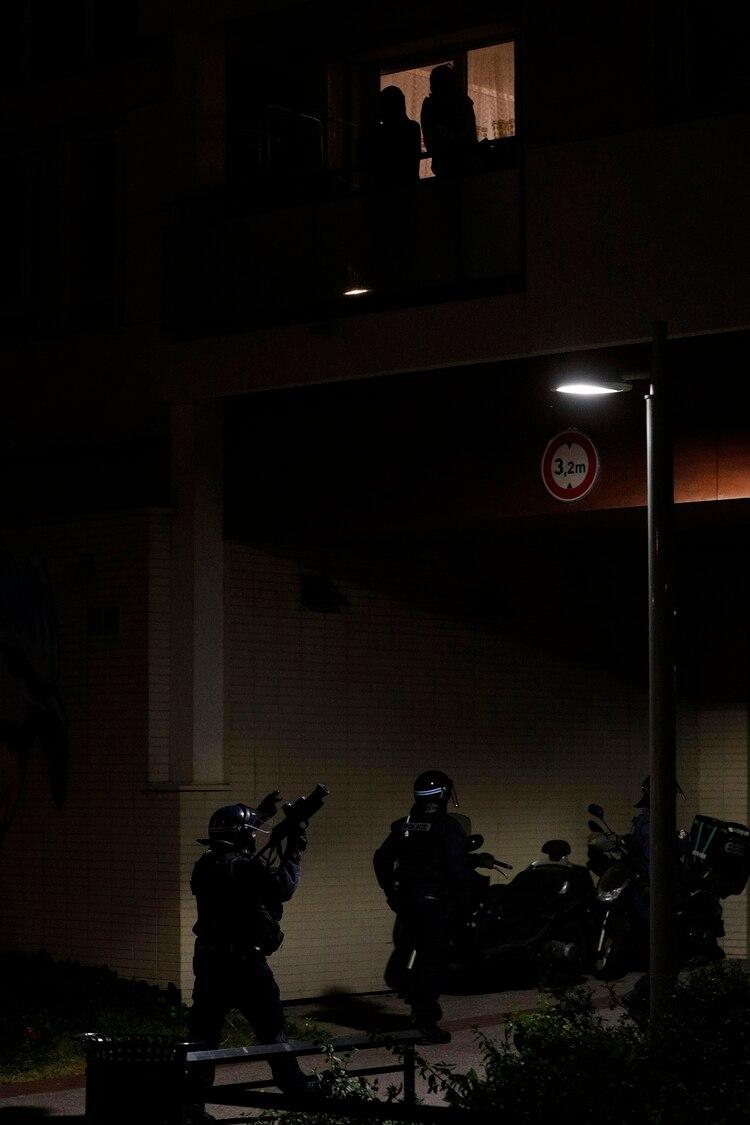 Vecinos observan el operativo policial en los suburbios de París (AFP)
