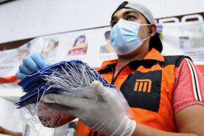 Un trabajador de Mero de la Ciudad de México reparte cubrebocas a los usuarios para evitar la propagación del Covid-19.  (Foto: EFE/ JOSE PAZOS)