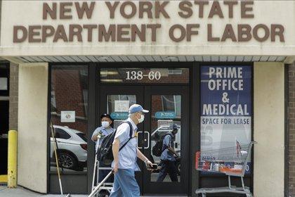 Transeúntes pasan frente a una oficina para el Departamento de Trabajo del Estado de Nueva York el jueves 11 de junio de 2020 (AP Photo/ Frank Franklin II)