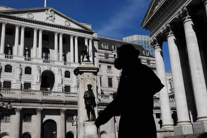 A person wearing a mask walks past the Bank of England, as the spread of the coronavirus disease (COVID-19) continues, in London, Britain, March 23, 2020. REUTERS/Toby Melville